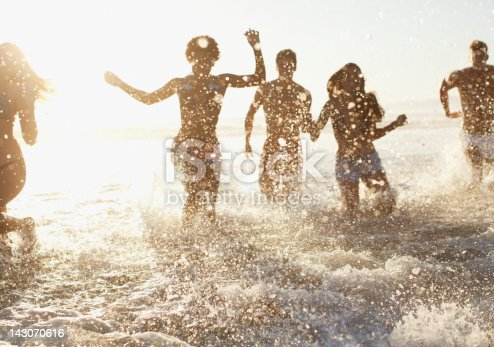 istock Friends playing in waves on beach 143070616