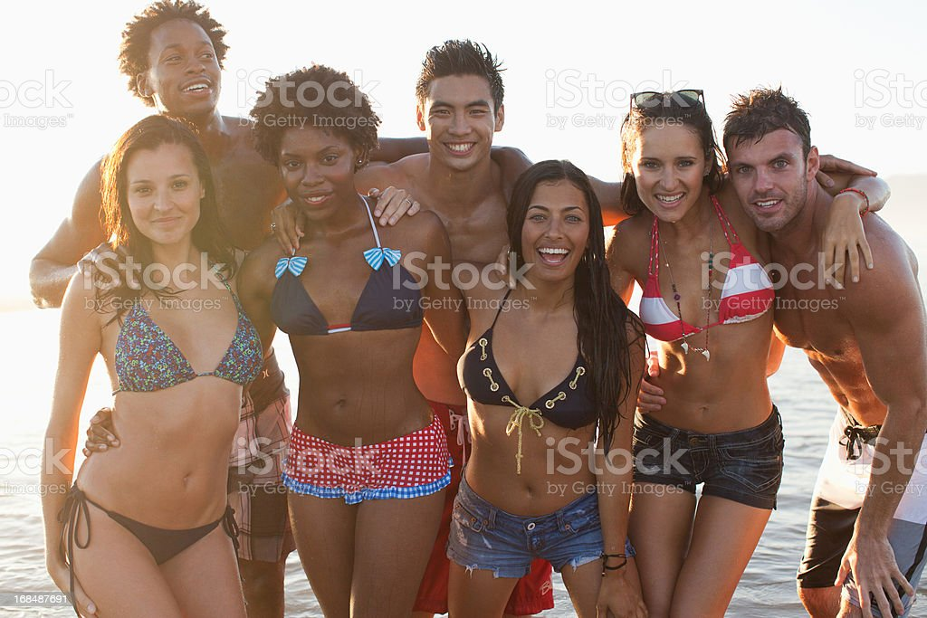 Friends playing in waves on beach stock photo