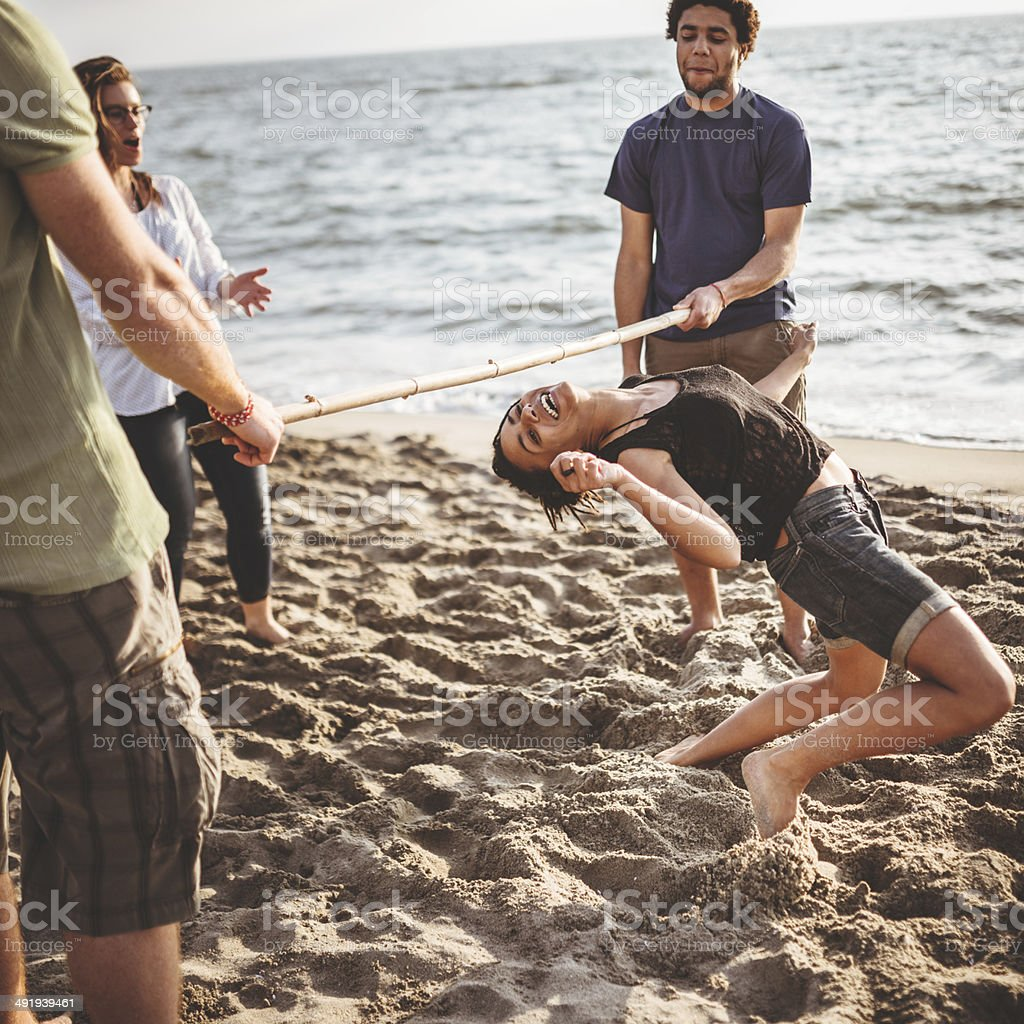 friends playing limbo on the beach stock photo