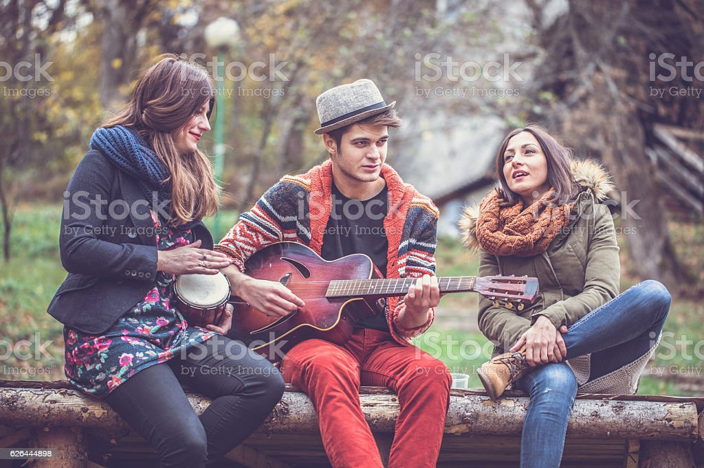 Friends playing music outdoors stock photo