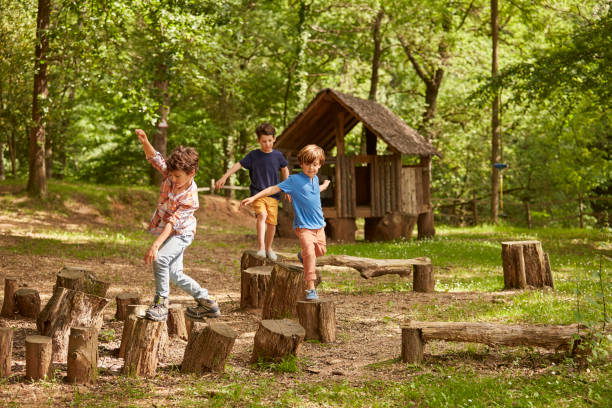 Friends playing on tree stumps in forest stock photo