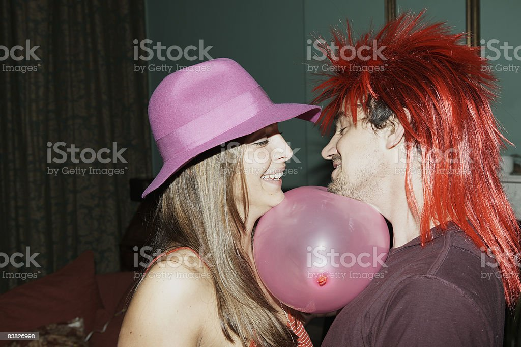 Friends playing passing game with balloon royalty-free stock photo
