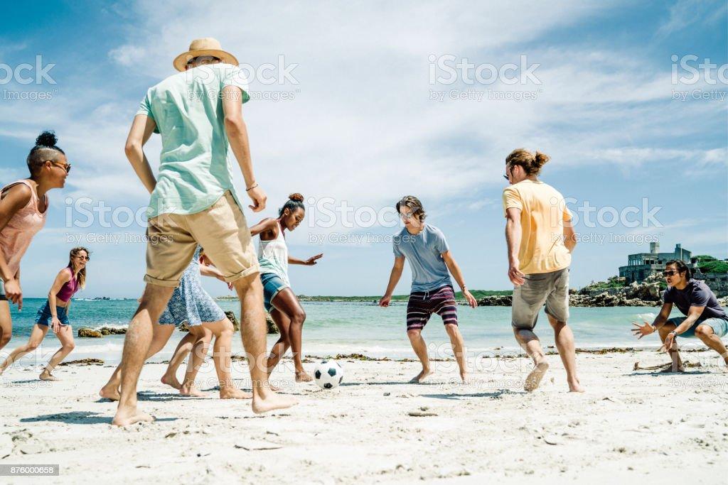 Freunden Fußball spielen am Strand bei Sonnenschein – Foto