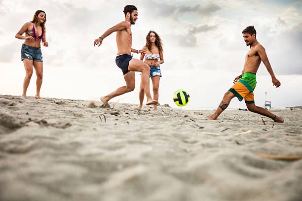 amigos jogando futebol durante férias na praia - futebol de areia - fotografias e filmes do acervo