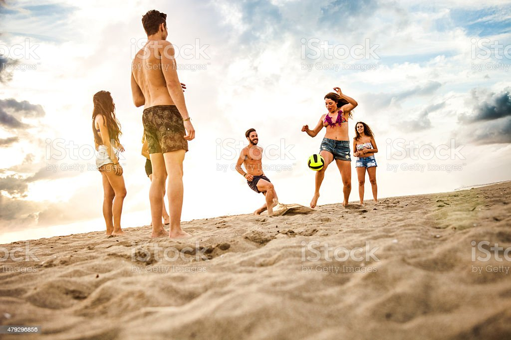Friends playing soccer on the beach stock photo