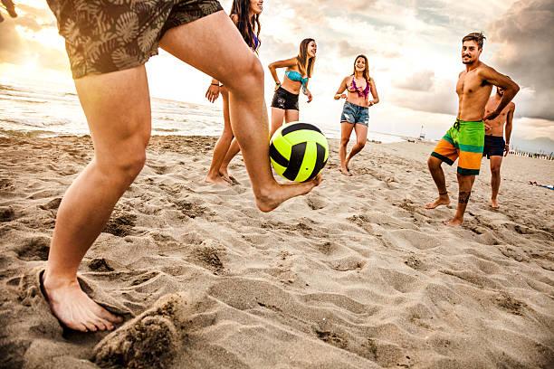 amigos jogando futebol na praia - futebol de areia - fotografias e filmes do acervo