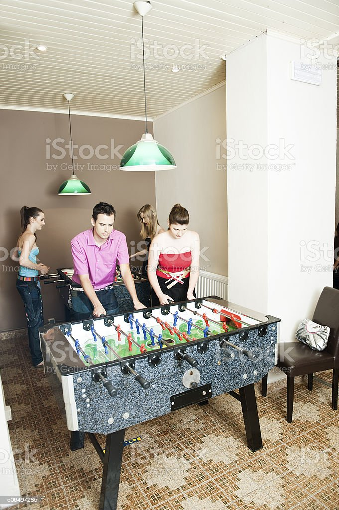 Friends playing table soccer stock photo