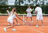 Happy group of friends playing tennis