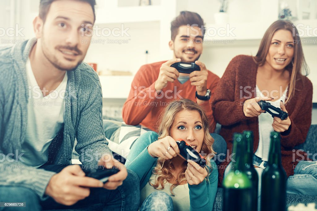 Friends playing video games at home stock photo