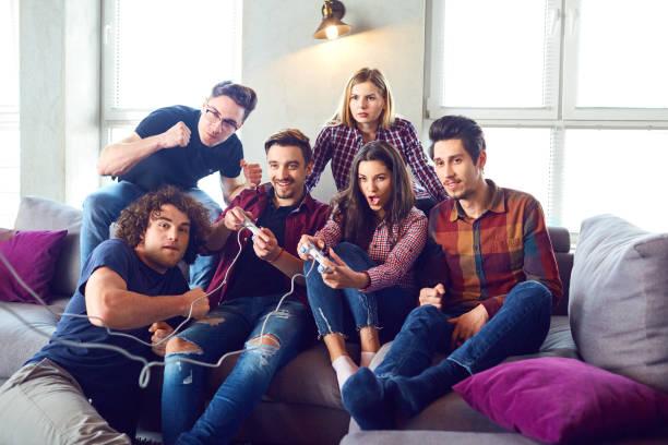 friends playing video games in the room - man joystick imagens e fotografias de stock