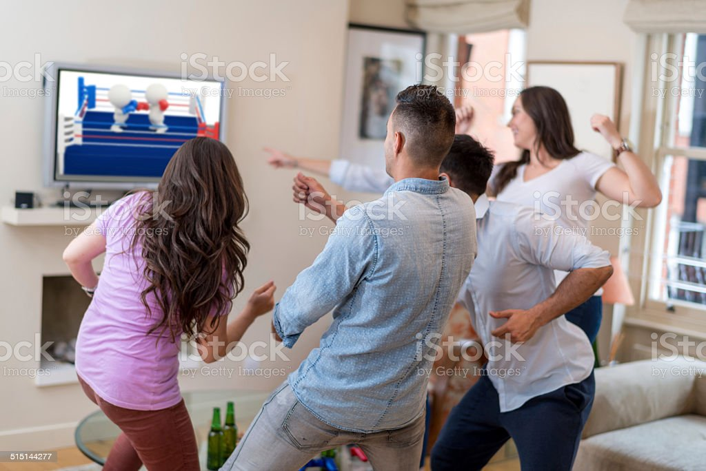 Friends playing video games - (own design on TV screen) stock photo