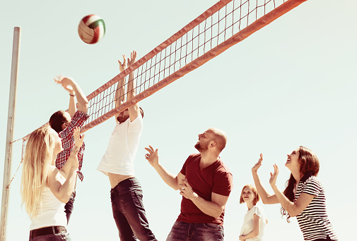 Positive heated friends playing volleyball at sandy beach