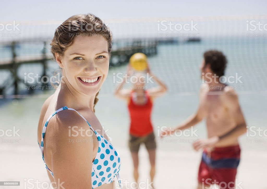 Friends playing volleyball at beach stock photo