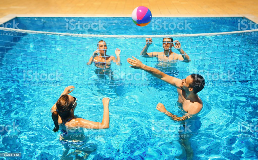 Friends playing volleyball in a pool. stock photo