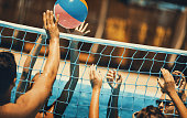 Closeup of group of people playing volleyball in a swimming pool.There are two couples tossing beach ball over the net. Toned image.