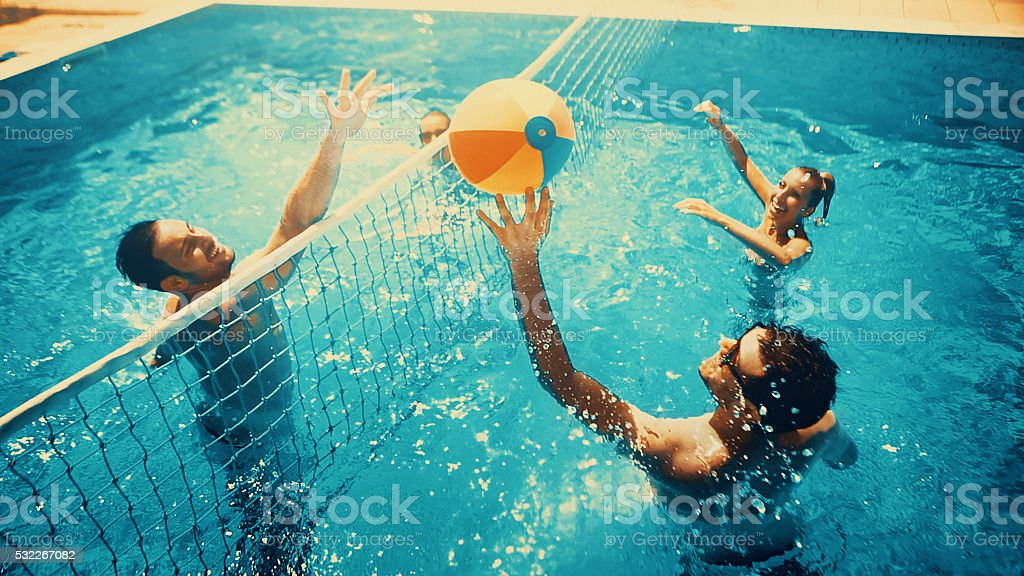 Amis, jouer au volley-ball dans la piscine. - Photo