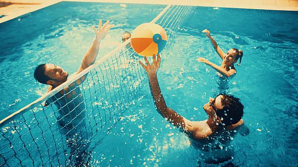 Amis, jouer au volley-ball dans la piscine. - Photo