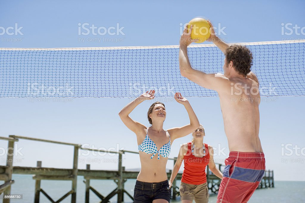 Friends playing volleyball on beach royalty-free stock photo