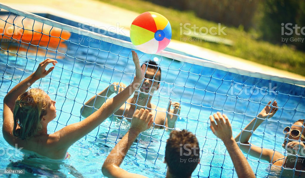 Friends playing volleybay in a pool. stock photo