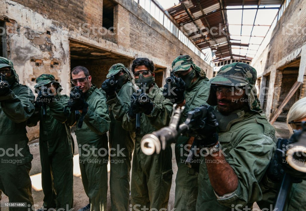 Friends playing warfare game with airsoft guns stock photo