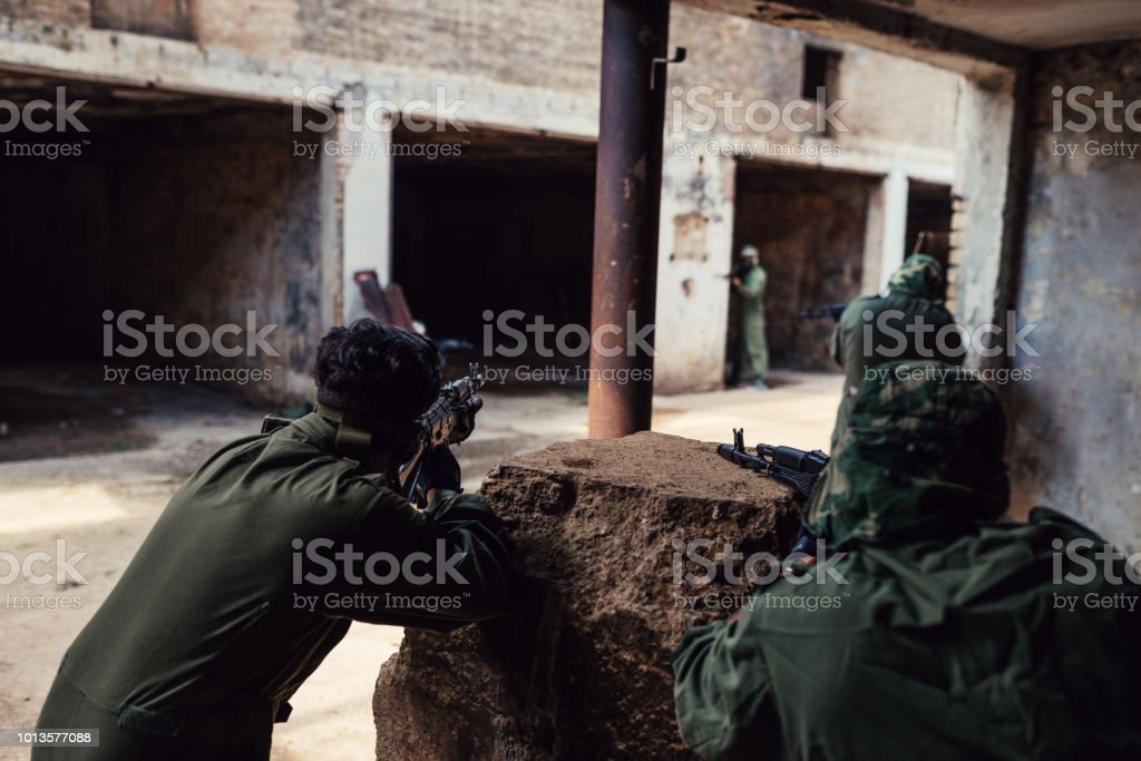 Friends playing warfare games on the battlefield stock photo
