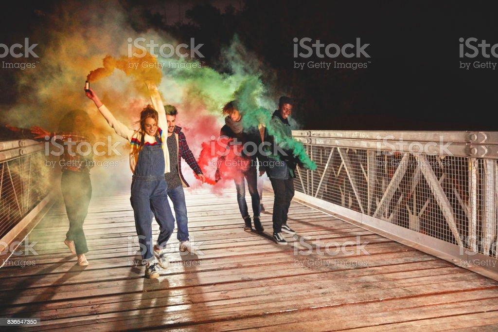 Amigos jugando con colores bomba de humo en puente - foto de stock