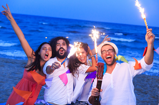 471113366 istock photo Friends playing with fireworks on a beach 489082788