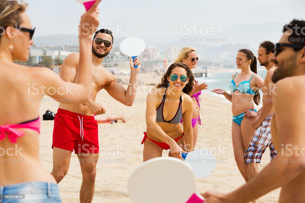Amici che giocano con racchette in spiaggia - foto stock