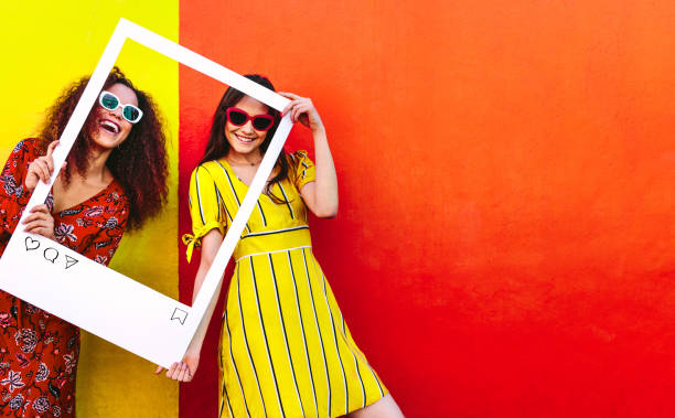 Friends posing for their social media post photo Portrait of two women holding a blank photo frame in hand and smiling. Girls wearing sunglasses standing against red and yellow colored wall. social networking stock pictures, royalty-free photos & images