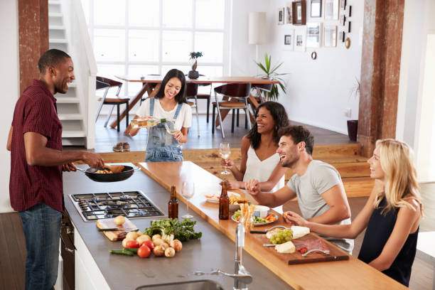 friends prepare and serve food for dinner party at home together - home cooking stock photos and pictures