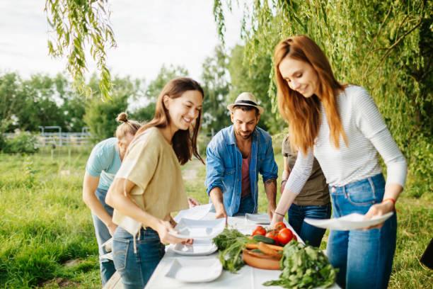 Amigos preparan almuerzo al aire libre en la granja Local - foto de stock