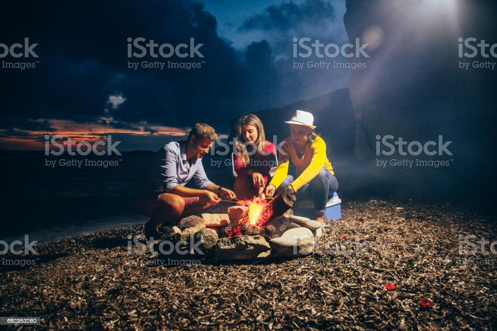 Friends prepare tasty sausages on campfire foto stock royalty-free