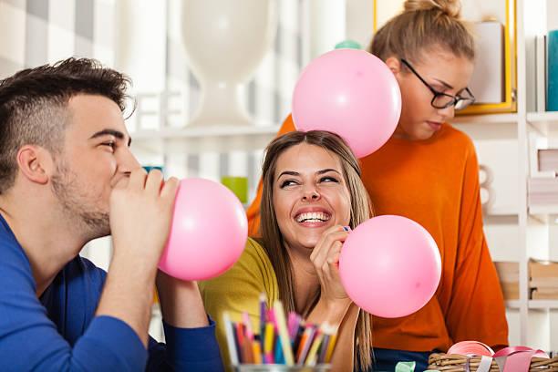 freunde, die vorbereitung für die party-ballons - jugendliche geburtstag geschenke stock-fotos und bilder