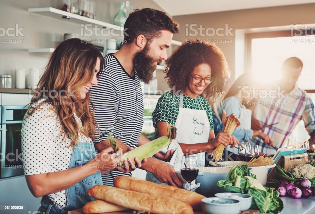 Friends preparing food at table in kitchen stock photo