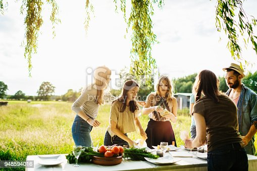 istock Friends Preparing Table Of Food Outdoors 948594016