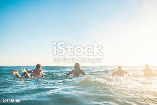Friends preparing to surf in the ocean