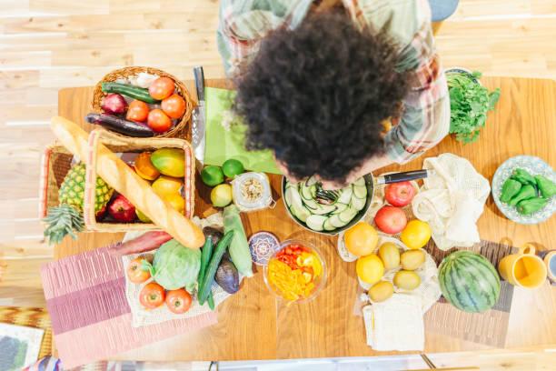 freunde bereiten vegetarisches essen für home-party - jamaikanische party stock-fotos und bilder
