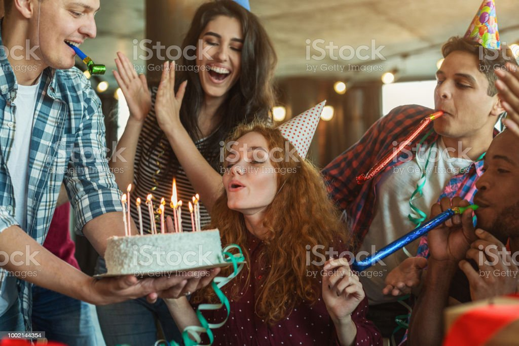 Friends presenting birthday cake to girl stock photo