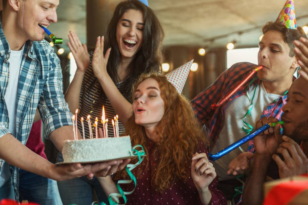 friends presenting birthday cake to girl - happy birthday stock pictures, royalty-free photos & images