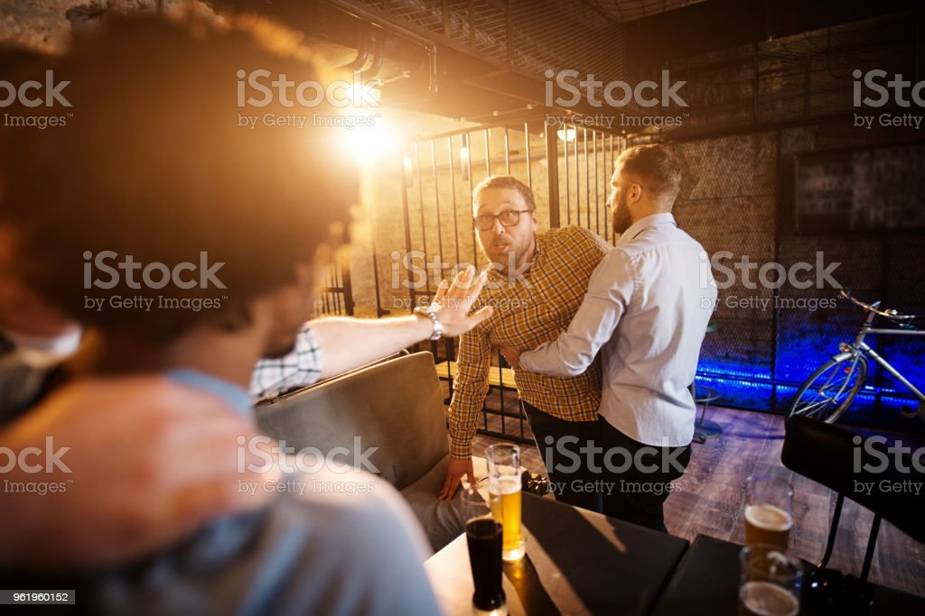 Friends preventing fighting and trouble of two mad guys in the bar. stock photo