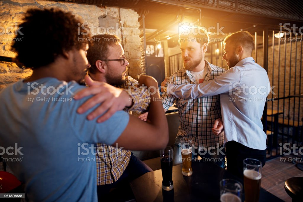Friends preventing fighting of two angry guys in the bar. stock photo