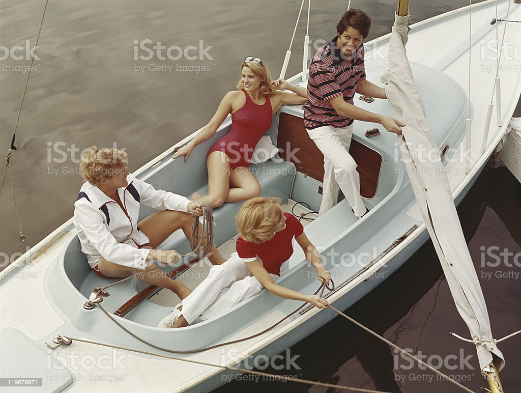 Friends pulling rope in sailing boat, smiling  stock photo