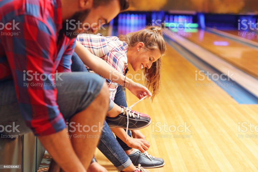 Friends putting on bowling shoes stock photo