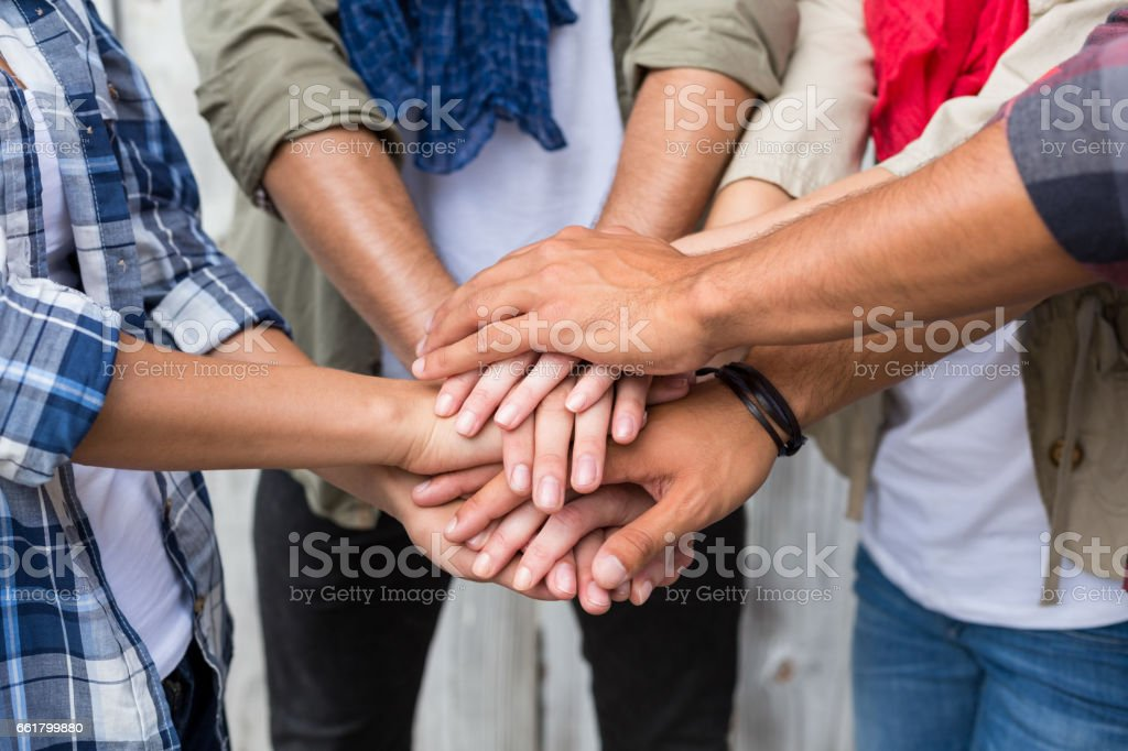 Friends putting their hands together stock photo