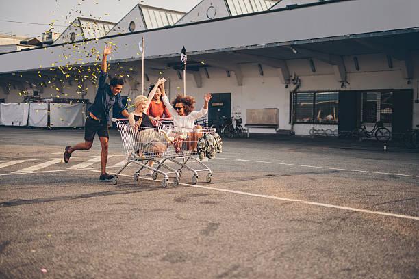 friends racing with shopping carts on road - beste freundin stock-fotos und bilder