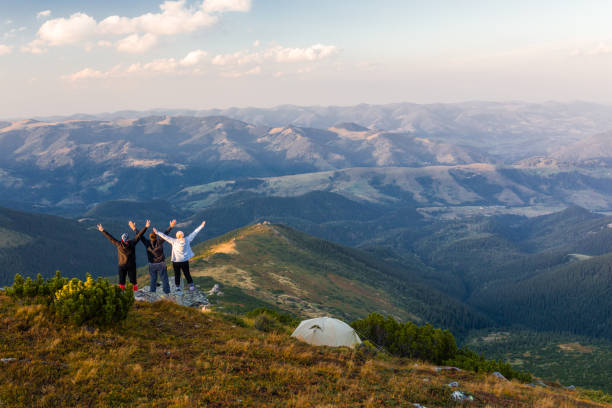 freunde heben die hand sich in bergen - zelt stehhöhe stock-fotos und bilder