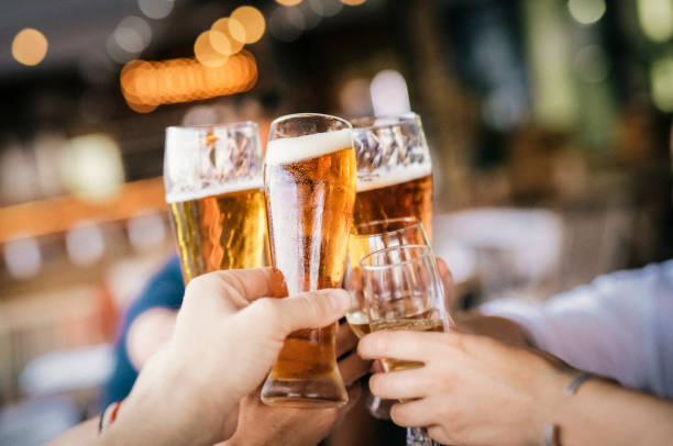 Friends raising celebratory toast during party Friends raising celebratory toast during party. Hands of man and woman are holding drinks. They are enjoying at restaurant. beer alcohol stock pictures, royalty-free photos & images