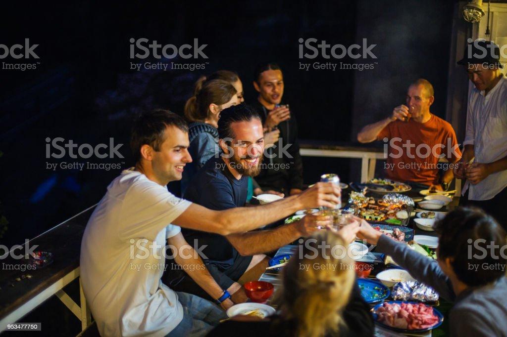 Amis, élever leurs verres pour porter un toast au cours d'un barbecue sur une terrasse - Photo