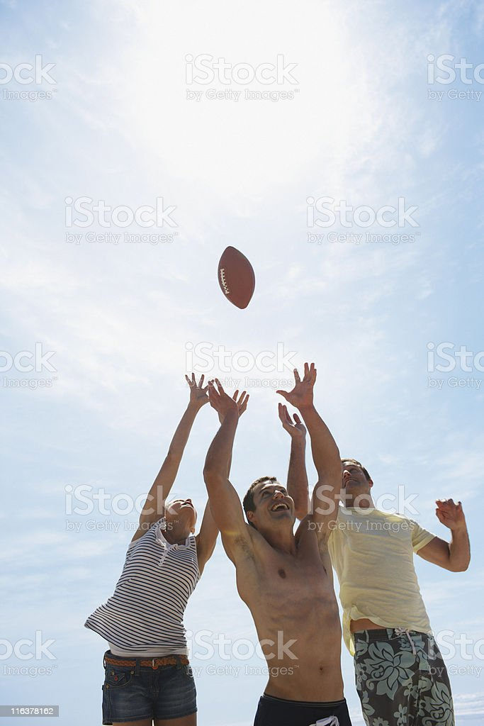 Friends reaching for football royalty-free stock photo
