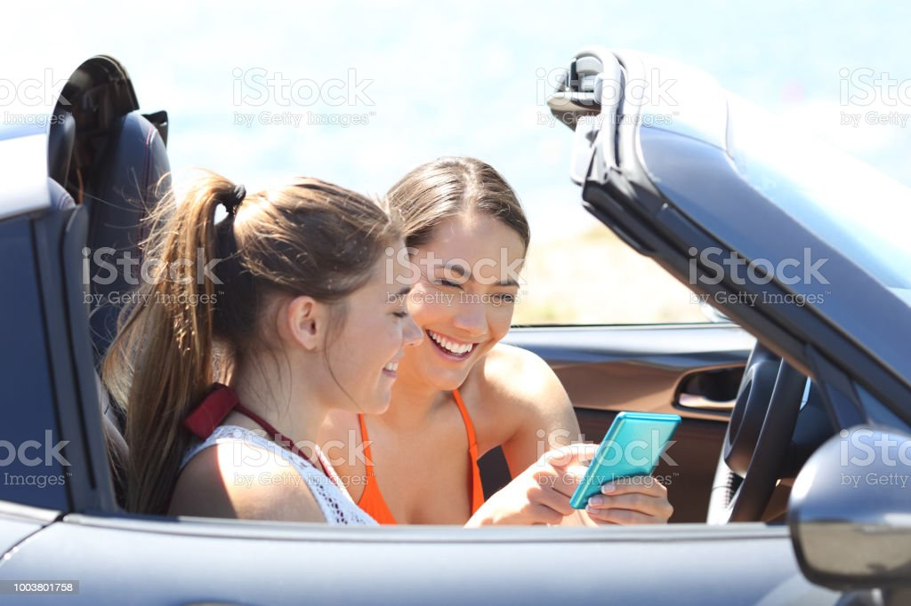 Two happy friends reading phone content inside a convertible car on...